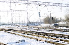 Railroad tracks in the snow. Commodity railway wagons, winter. High-voltage wires above the railway tracks. Beautiful sunset light royalty free stock photos