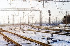 Railroad tracks in the snow. Commodity railway wagons, winter. High-voltage wires above the railway tracks. Beautiful sunset light royalty free stock photo