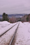 Railroad tracks in the snow. Railroad tracks in winter and foggy sky over Mount Orford, Quebec Royalty Free Stock Photography