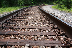Railroad tracks stretch into forest. Close-up of railroad tracks, then curve to the right and stretch into forest royalty free stock images