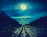 Free Railroad Tracks Through The Woods At Night. Beautiful Sky And Full Moon Above Silhouettes Of Trees And Railway. Serenity Nature Royalty Free Stock Images - 131503349