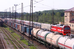 Railroad tracks with train with containers and cisterns and passenger train Stock Photography