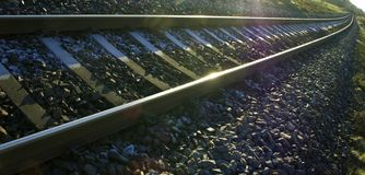 Railroad tracks in interesting long perspective with sun shining from the side all way on the track. stock image