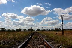 The railroad tracks. Are visible to the sky and there are grasses along the way stock photography