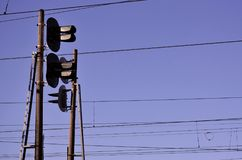 Railroad traffic light against clear blue sky, Contact wire. High voltage railroad power lines on neutral blue sky background wit. H traffic lights stock photography
