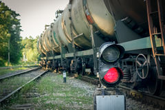 Railroad traffic light. And freight train on behind Stock Photo