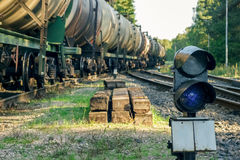 Railroad traffic light. And freight train on behind Stock Photos