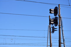 Railroad traffic light and overhead lines. Railroad traffic light against clear blue sky, Contact wire. High voltage railroad power lines on neutral blue sky Royalty Free Stock Photos