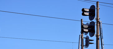 Railroad traffic light and overhead lines. Railroad traffic light against clear blue sky, Contact wire. High voltage railroad power lines on neutral blue sky Royalty Free Stock Photo