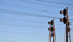 Railroad traffic light and overhead lines. Railroad traffic light against clear blue sky, Contact wire. High voltage railroad power lines on neutral blue sky Stock Photography