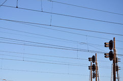 Railroad traffic light and overhead lines. Railroad traffic light against clear blue sky, Contact wire. High voltage railroad power lines on neutral blue sky Royalty Free Stock Photography