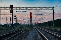 Railroad traffic lights and infrastructure during beautiful sunset, colorful sky, transportation and industrial concept Royalty Free Stock Photo