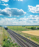 Railroad with train and clouds Royalty Free Stock Photography