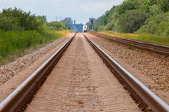 Railroad with train in the distance. Railroad in rural landscape with train in the distance Royalty Free Stock Images