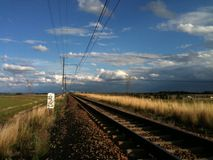 Railroad with train passing in the distance. Electric train on railroad at sunset with dramatic clouds in nature Stock Photo
