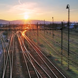 Railroad with train at sunset and many lines Royalty Free Stock Photos