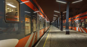 Railroad travel and transportation industry business concept: summer night view of two high speed modern passenger. Trains departing from railway station Royalty Free Stock Photo