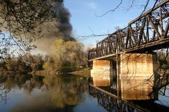 Railroad Trestle Fire SACRAMENTO, CALIFORNIA UNITED STATES MARCH 15, 2007. Black clouds of smoke billow into the blue sky as a railroad trestle burns in Royalty Free Stock Image