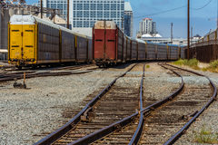 Railroad. Two trains and two rail roads junction and skyscraper Royalty Free Stock Images