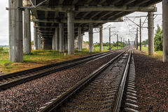 Railroad under highway bridge. Two of the railroad under highway bridge in cloudy rainy weather Stock Images