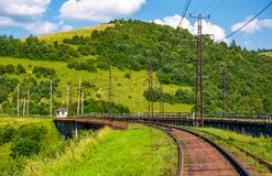 Railroad viaduct through forested hills in summer. Lovely transportation scenery in Carpathian mountains, Skotars`ke, Ukraine Stock Photography