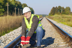 Railroad worker with adjustable wrench. On railway Royalty Free Stock Photo