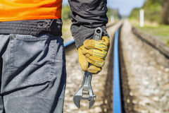 Railroad worker with adjustable wrench on railway in spring. In summer day Royalty Free Stock Image