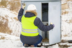 Railroad worker checking electrical enclosures. In winter day royalty free stock photography