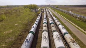 Railroad yard with trains with tanks amidst the fields. Aerial view stock footage