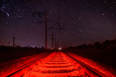 Rails against the starry sky with unusual red illumination Royalty Free Stock Photos