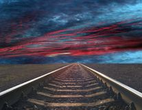 Rails going away into the landscape distance. Rails going away into the gloomy landscape. Black and white image with rails going away into the dark sky landscape Royalty Free Stock Images