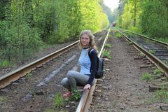 The girl is sitting on the rails. Rails going into the distance. road in perspective.rails passing through the forest. the girl is sitting on the rails Stock Photography