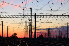 Rails railway line In dark during pink sunset and poles with wir Royalty Free Stock Images
