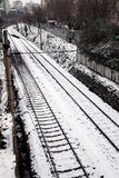 Rails in the snow. Rails covered with snow, also some buildings and trees are visible Royalty Free Stock Images