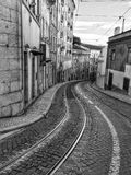 Rails in the street. Stoned curve street in Lisbon with tram rails running ahead. Very common view on Lisbon streets with old rails of main tourist attraction Stock Photography