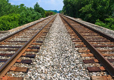 Rails to Infinity. Two sets of railroad tracks run straight and parallel to a vanishing point on the horizon with green trees along side Royalty Free Stock Photos