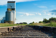 Railway. A railway going to a prairie grain elevator shot on a partly cloudy day Stock Photo