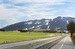 Railway and Alps mountains. Scenic view of road and railway track receding through countryside with snow capped Alps mountains in background, Germany Royalty Free Stock Photo