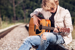 Railway blues. Young man plaing on guitar on the railway Royalty Free Stock Photos