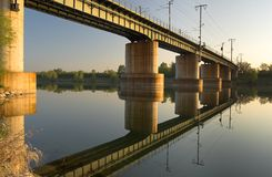 Railway bridge. The shot was taken in the early morning, the reflection of the bridge can be seen in the water Royalty Free Stock Photos