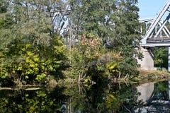 Railway bridge across the river in autumn. Stock Photo