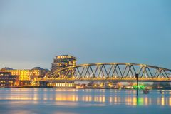 Railway bridge, apartments, houses and offices in the Dutch city. Of Nijmegen with the flooded river Waal in front Royalty Free Stock Images