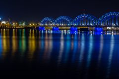 Railway Bridge crosses the Daugava river in Riga at night. Panoramic view on Riga the capital of Latvia city from left bank of royalty free stock images