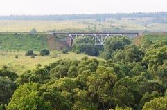 Railway bridge and green trees foreground Stock Photos
