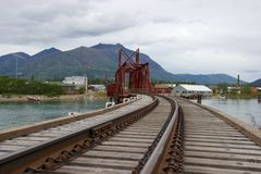 Railway bridge and mountains in Carcross, Yukon. Carcross (short for Caribou Crossing) is a small town in the Yukon Territory about a one-hour drive from the Royalty Free Stock Photography