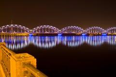 Railway bridge at night in Riga stock photography