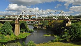 Railway bridge over the beautiful river, on which the train goes royalty free stock photos