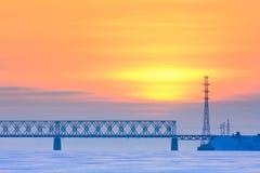 Railway bridge over a frozen river Royalty Free Stock Image