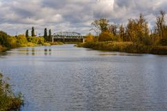 Railway bridge over the river against the background of autumn forest Stock Photography