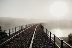 Railway bridge over a river in a foggy day. Royalty Free Stock Photos